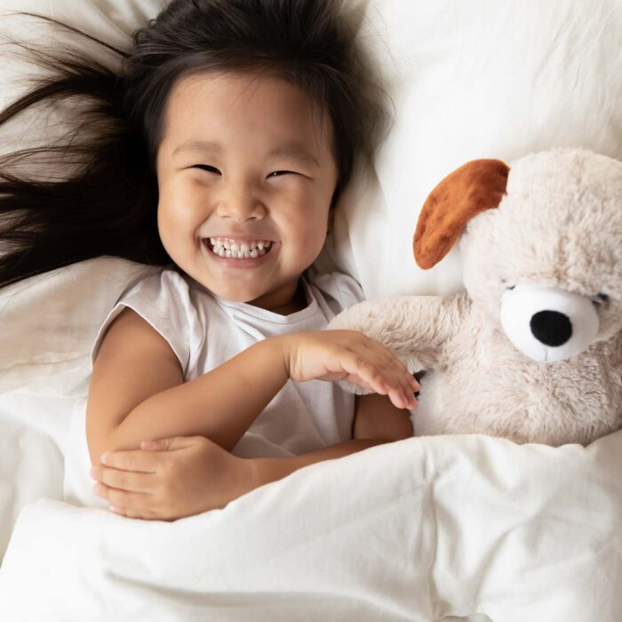 Smiling girl with stuffed dog toy in bed