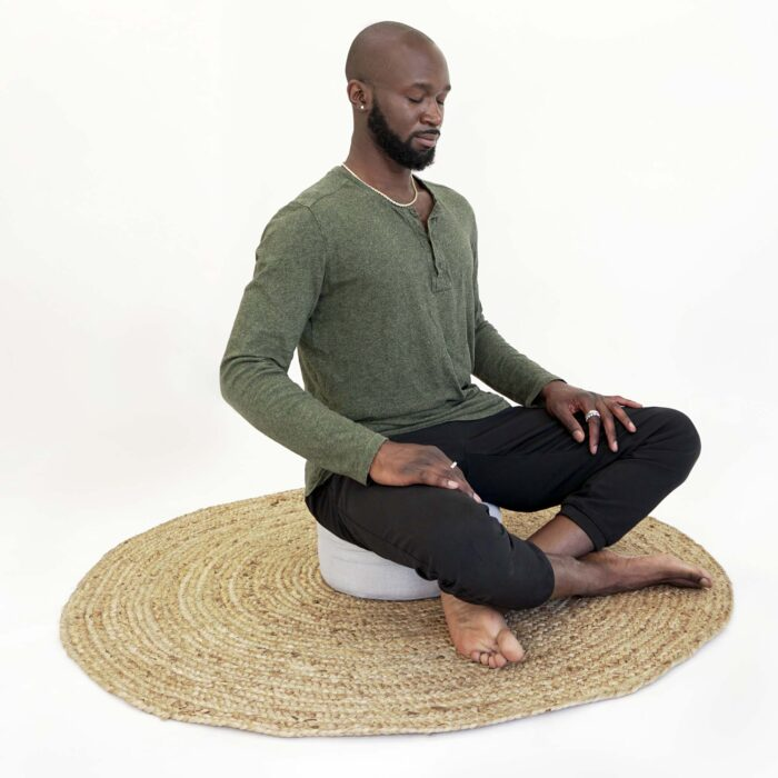 man meditating on pillow with legs crossed