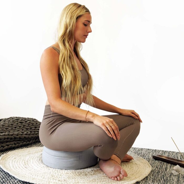 woman meditating on pillow with legs crossed