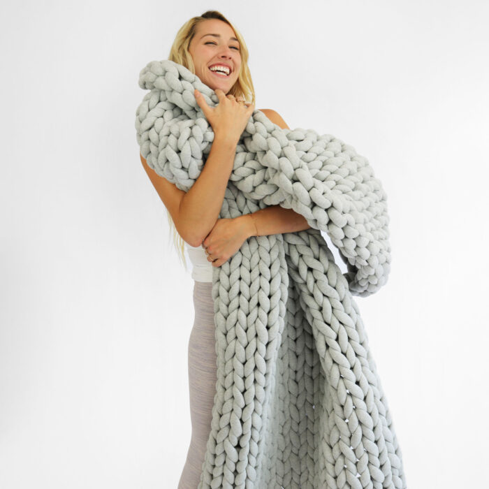 woman holding weighted blanket standing and smiling