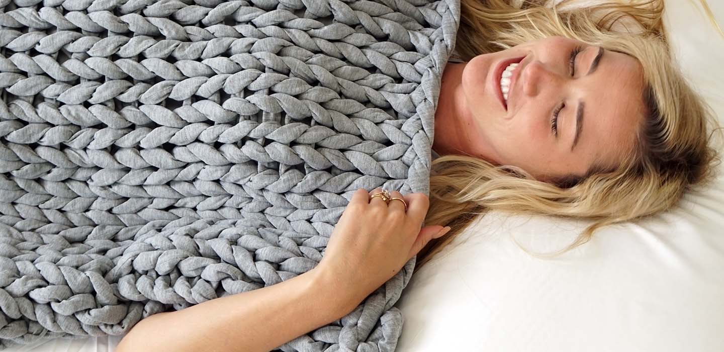 woman smiling under weighted blanket