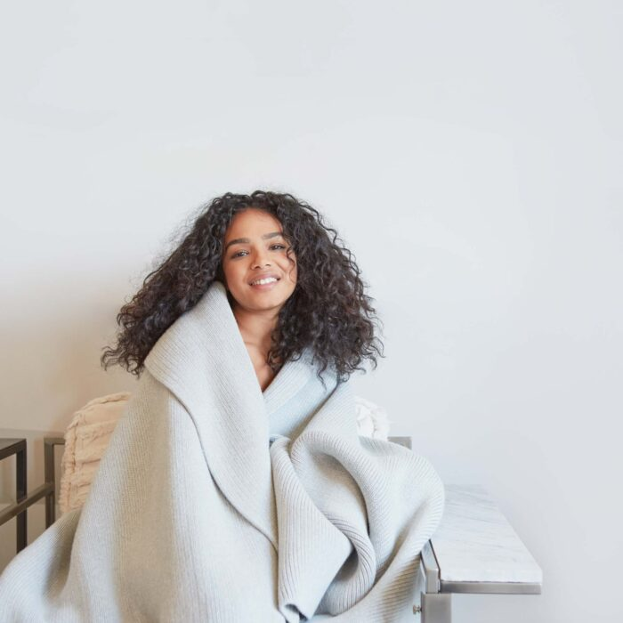 Woman wrapped in weighted blanket.